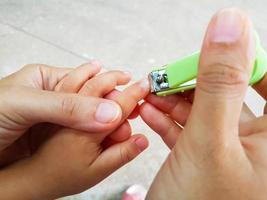 gros plan mère coupant les ongles pour son bébé photo