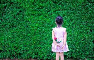 petite fille en robe reculer et tenant une rose rouge dans le parc photo