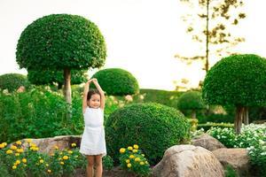 petite fille debout sur le rocher et mains ouvertes avec le coucher du soleil photo