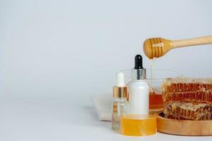 savon et sérum de soin de la peau naturels au miel et nid d'abeille posés photo