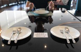 les gens gardent une distance sociale tout en déjeunant au restaurant photo