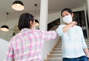 personnes portant un masque et se cognant le coude pendant la pandémie photo
