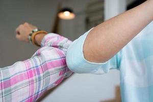 femme faisant des salutations en toute sécurité en se cognant le coude pendant l'épidémie de covid 19 photo