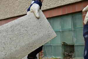 le maçon met des blocs préfabriqués en béton sur le mur photo