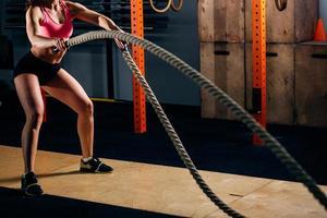 jeune femme athlétique faisant des exercices de cross fit avec une corde en plein air photo