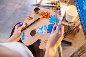artiste femme mélangeant les couleurs à l'huile sur la palette photo