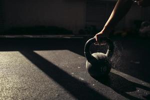 modèle féminin prendre une bouilloire avec de la poudre de talc dans une salle de sport photo