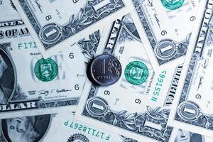 une pièce de rouble dans le contexte des notes de dollars américains. photo