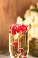vin mousseux en verre avec des baies de groseille rouge photo