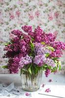 bouquet de lilas violet dans un vase. nature morte aux branches de lilas. photo