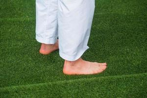 photo d'un homme aux pieds nus assis sur l'herbe verte fraîche