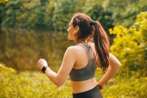 La photo en gros plan d'une jeune femme qui court à l'extérieur au coucher du soleil dans le parc