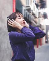 heureuse jeune femme asiatique écoutant de la musique photo