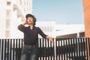heureuse jeune femme asiatique écoutant de la musique avec des écouteurs photo