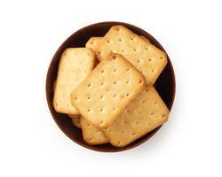 Biscuits craquelins dans un bol en bois isolé sur fond blanc photo