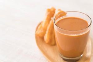 bâton de pâte frit avec du thé au lait sur bois photo