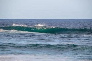 vague déferlant sur la troisième dalle de la plage d'arpoador à rio de janeiro. photo
