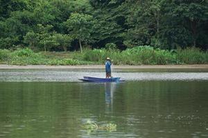 l'homme solitaire se tient sur le bateau et récupère le poisson du filet photo