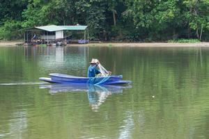 l'homme solitaire s'assied dans le bateau et récupère le poisson du filet photo