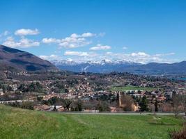 vue panoramique sur le lac, les montagnes enneigées et une petite ville photo