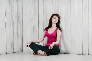 une jolie fille dans un haut rose, assise sur le sol dans la détente photo