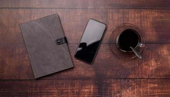 tasse à café, livre, téléphone intelligent sur le bureau. photo