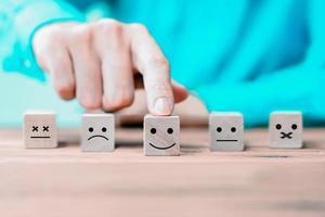 l'homme d'affaires choisit un visage heureux d'icônes d'émoticônes sur un bloc de bois. photo