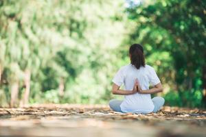 jeune femme asiatique faisant du yoga le matin au parc. photo