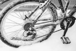 roue de vélo dans la neige et la glace en gros plan par temps froid d'hiver photo