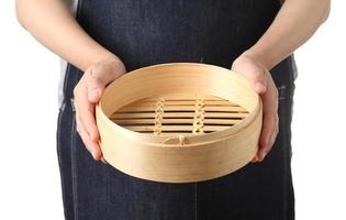 Chef tenant un panier de boulettes de bambou chinois vide sur fond blanc photo