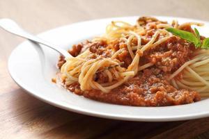 fermer une fourchette avec des spaghettis et de la sauce rouge dans un plat blanc photo