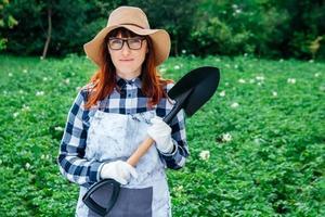 agricultrice avec une pelle sur fond de jardin verdoyant photo