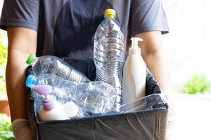 Femme tenant des ordures de bouteilles en plastique dans une boîte pour réutiliser le recyclage photo