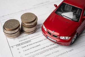 voiture et pièces de monnaie sur le formulaire de voiture d'accident de réclamation d'assurance photo