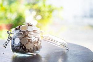économiser des pièces d'argent dans un pot d'herbe, concept d'investissement en finance d'entreprise. photo
