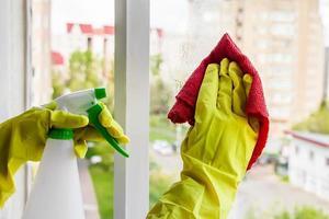 femme dans des gants en caoutchouc jaune essuie le verre photo