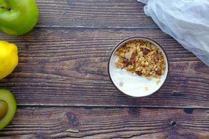 Petit déjeuner de céréales de yaourt dans un bol sur fond de bois photo