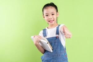 Portrait d'enfant asiatique tenant un livre sur fond vert photo