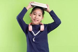 Portrait d'enfant asiatique tenant un livre sur bkacground vert photo