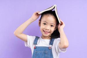 Portrait d'enfant asiatique tenant un livre sur fond violet photo