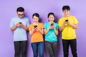 groupe de meilleurs amis asiatiques utilisant un téléphone portable sur fond violet photo