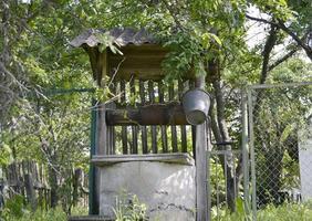 Puits avec seau en fer sur une longue chaîne forgée pour une eau potable propre photo
