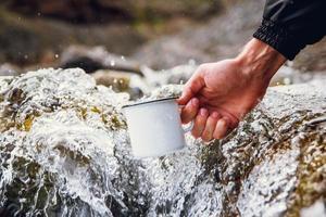 la main de l'homme tient une tasse en métal sur fond de rivière photo