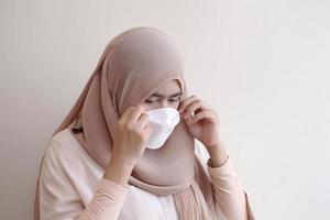 fille musulmane portant un masque chirurgical sur fond pastel. photo