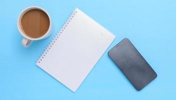 tasse à café, livre, smartphone sur fond bleu photo