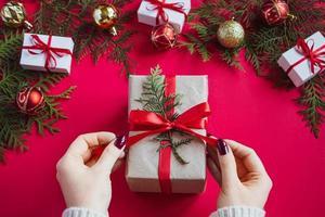 les mains tiennent une belle boîte-cadeau avec un arc sur fond rouge photo