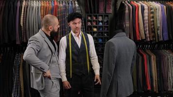 ralenti du bel homme choisissant un costume avec tailleur en atelier. designer présentant le costume sur le menequin à l'acheteur photo