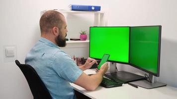 homme d'affaires travaillant et tapant sur un téléphone portable et un ordinateur avec deux moniteurs écran vert de travail multitâche photo