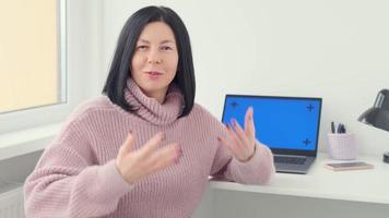 femme assise à table avec un ordinateur portable. représentante du vlogger féminin parlant, expliquant devant la caméra et faisant des gestes à la maison. commerce, affaires. photo