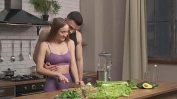jeune couple musclé préparant un cocktail sain après l'entraînement, parlant et riant dans la cuisine. sport, régime, concept d'alimentation saine, ralenti photo